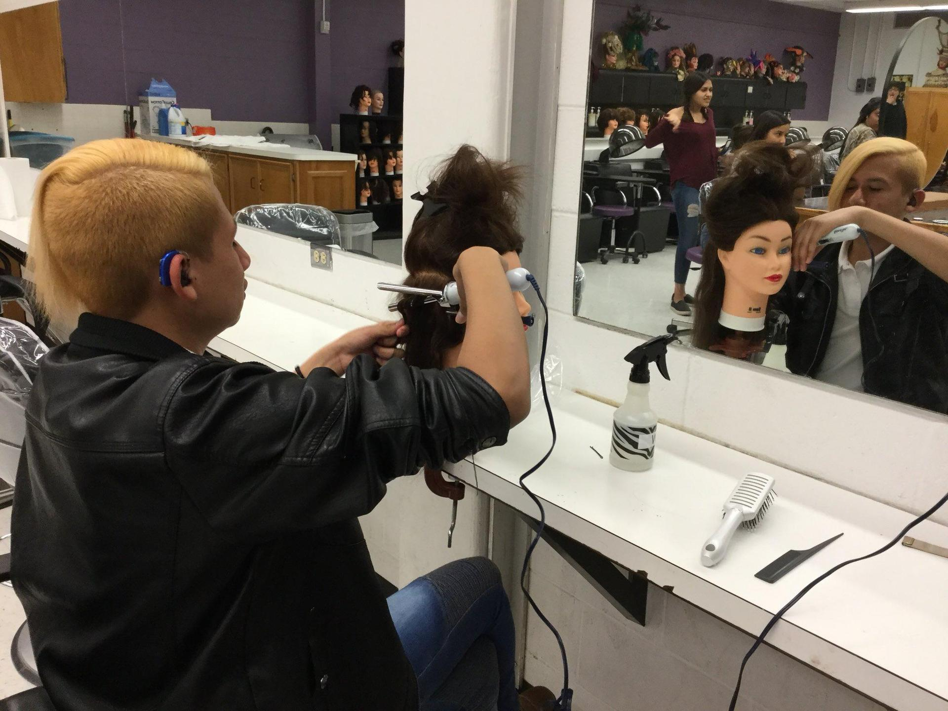 student styling a mannequin's hair