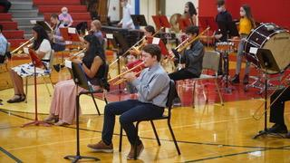 A group of students playing band instruments in the Benjamin gym. The focus is on a student playing trumpet.