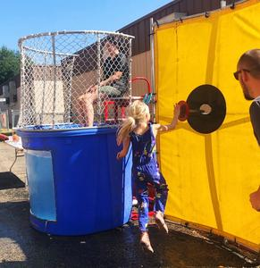 Girl jumping up to push target at dunk tank.
