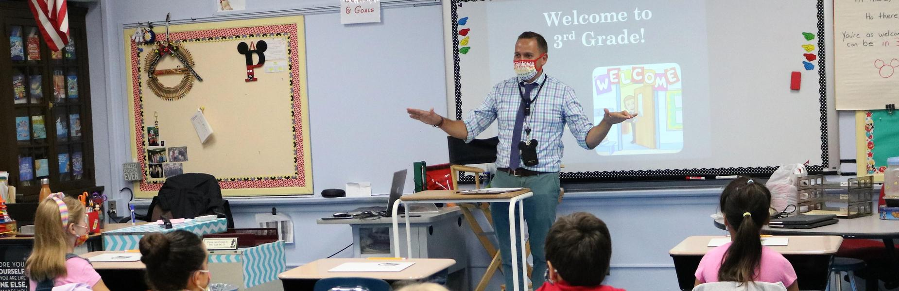Photo of 3rd grade teacher speaking to class on first day of school.