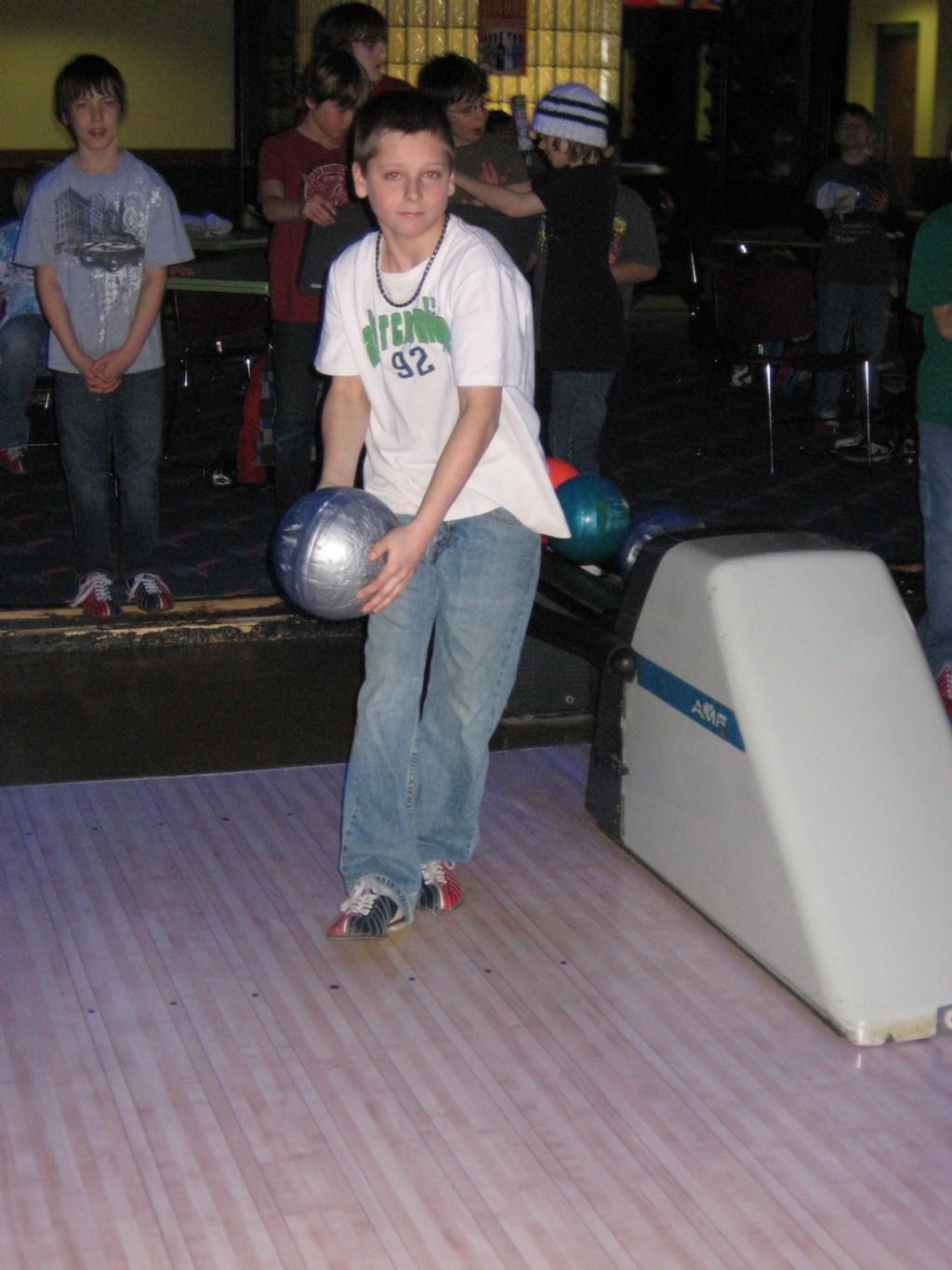 boy holds bowling ball with both hands