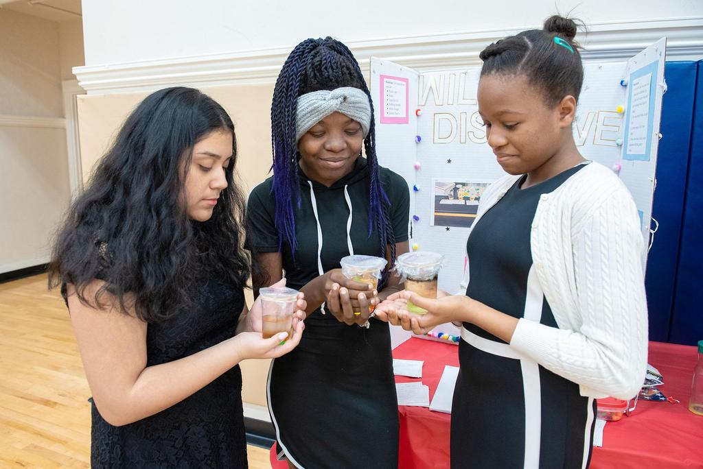 Three students each hold and look into cups filled with liquid