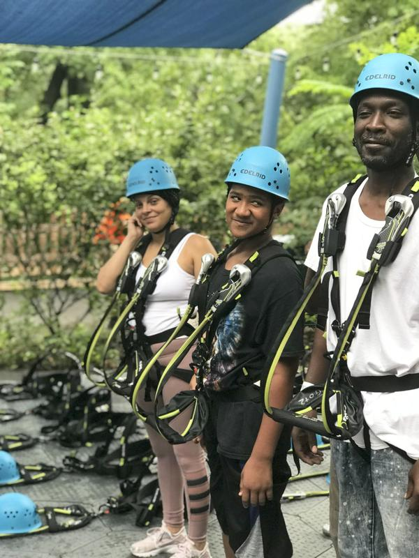 A student and 2 staff members looking eager for the zipline adventure