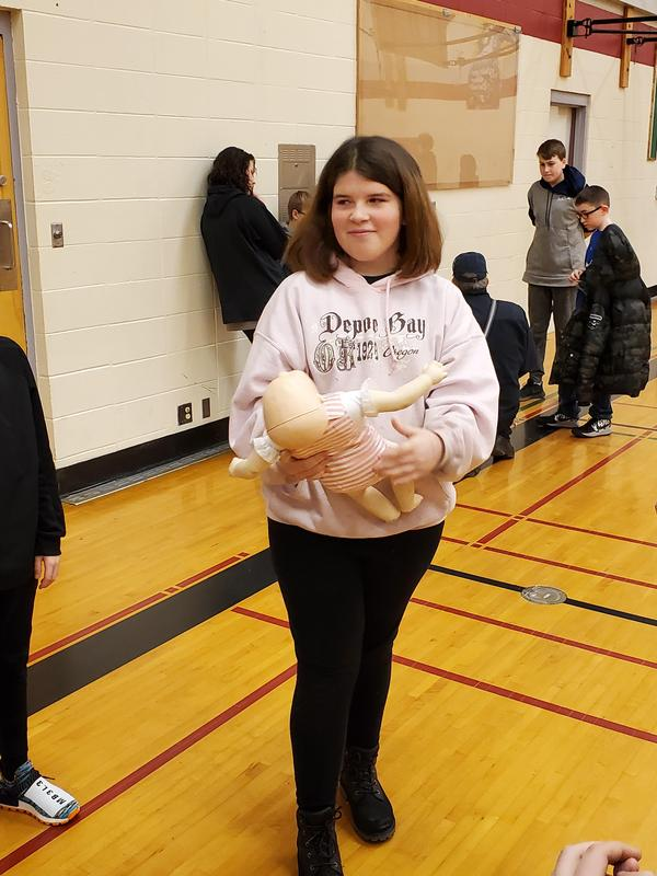 student showing cpr doll