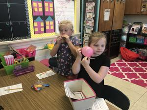 Students experiment with sound using balloons.