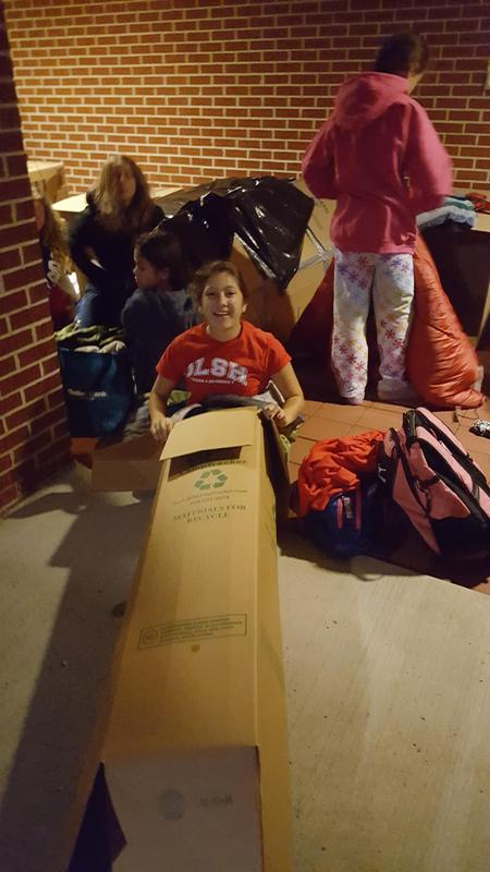 A student gets into a cardboard box to sleep for the night at the OLSH Box Out event