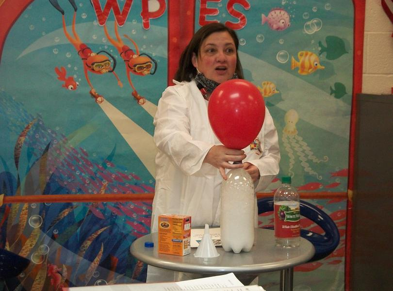 Ms. Church demonstrating a science experiment.