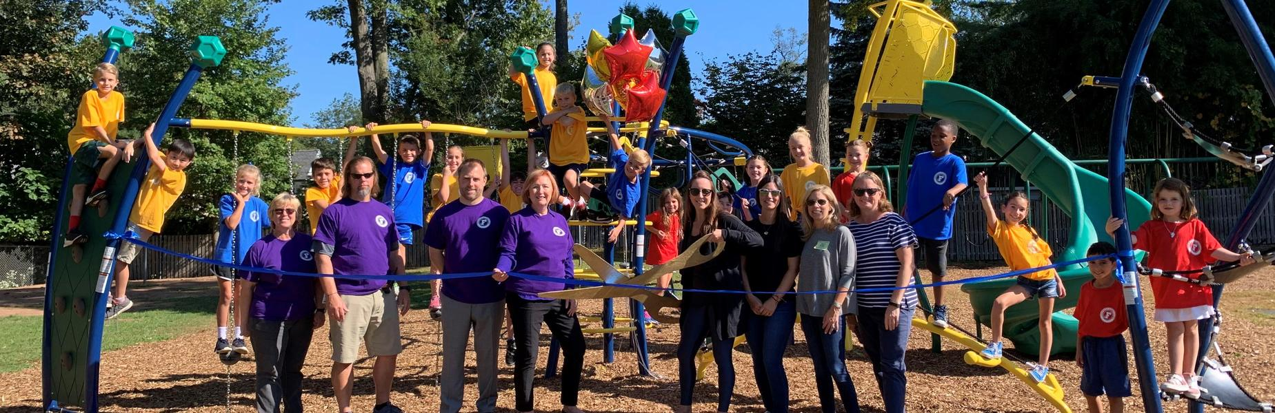 Photo of Franklin School staff and students posing with new playground addition during ribbon cutting ceremony.