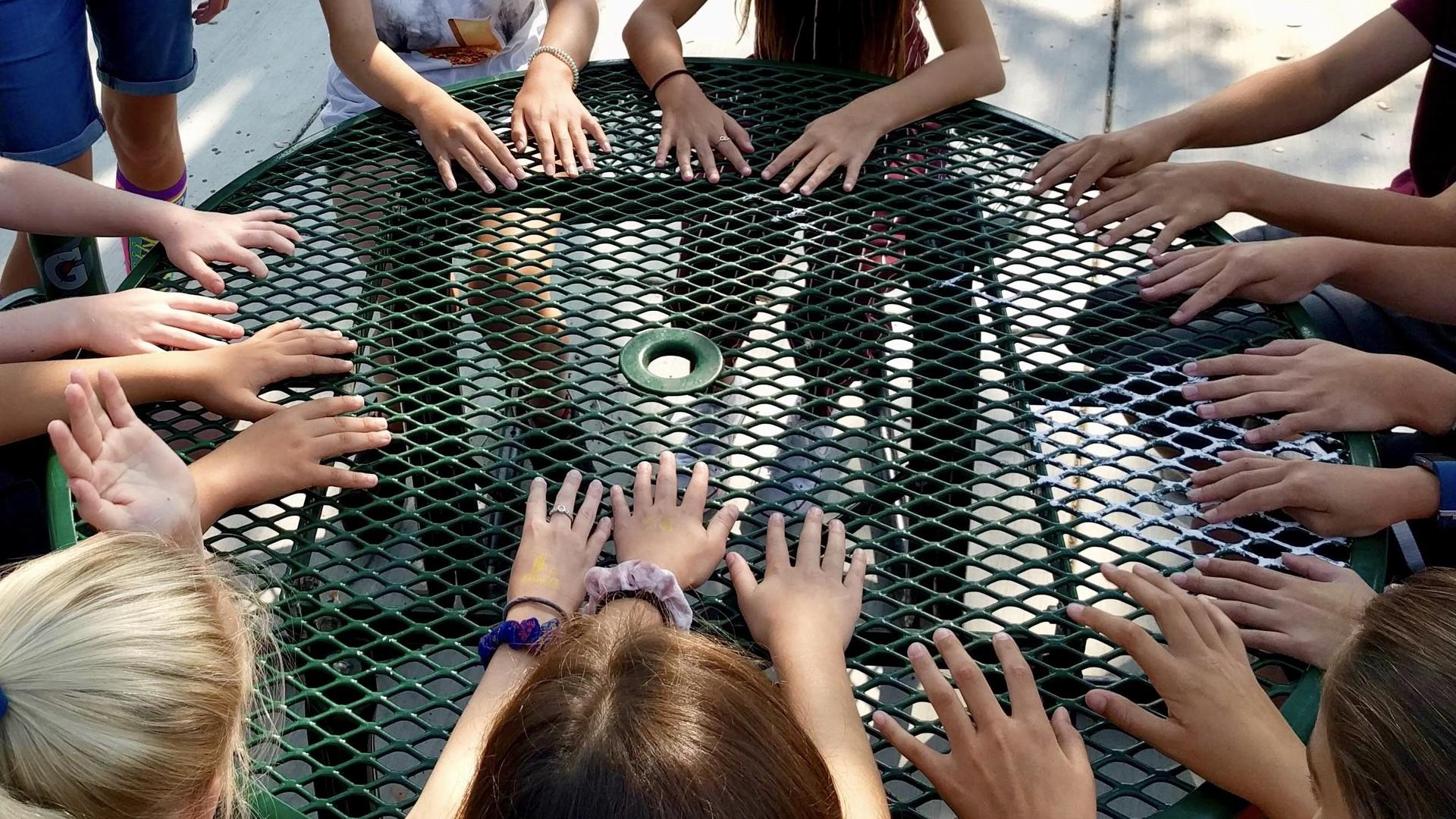 Hands around table