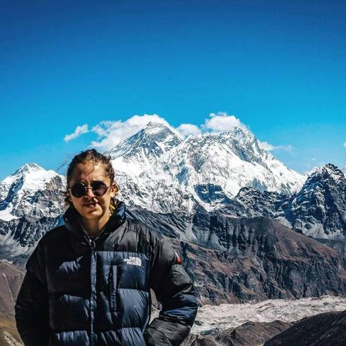 I love to be outside. This is a picture of me with Mount Everest in the background!