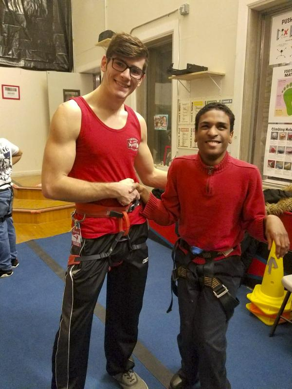 Student with his trainer at the rock climbing facility