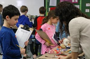 """Photo of Franklin 2nd graders examining Chinese artifacts.  Chinese artifacts, on loan from the Morris Museum, gave Franklin 2nd graders the chance to learn about Chinese culture during """"China Day"""" on Feb. 21.  The study of China is part of a 2nd grade unit on cultural diversity."""