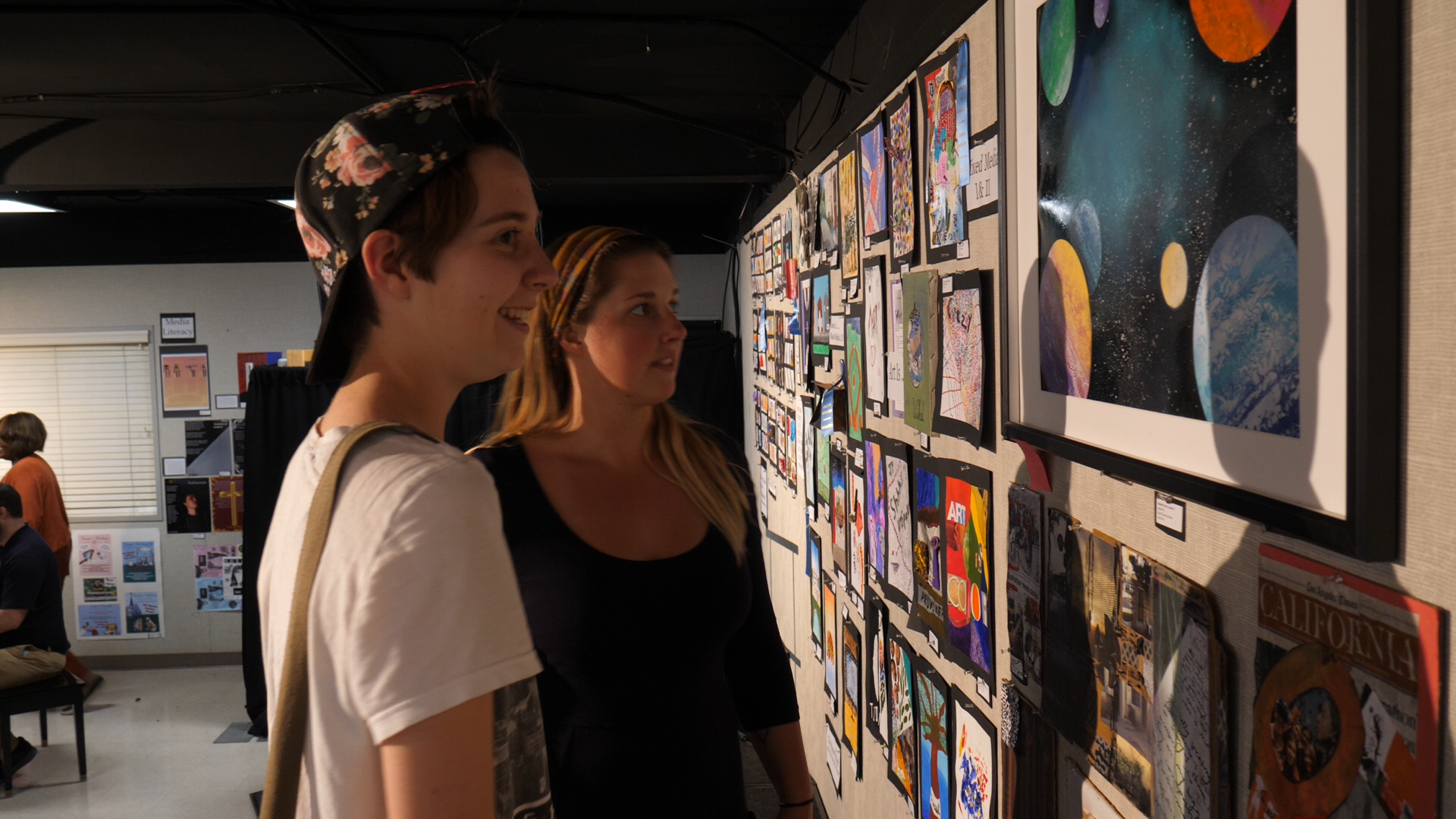 Ms. Sullivan reflecting on an art project with a student at the all-school art show.