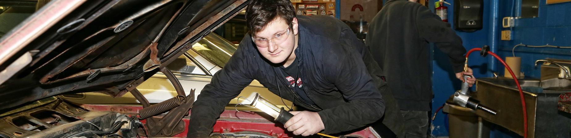 LHS student working on a car in auto shop