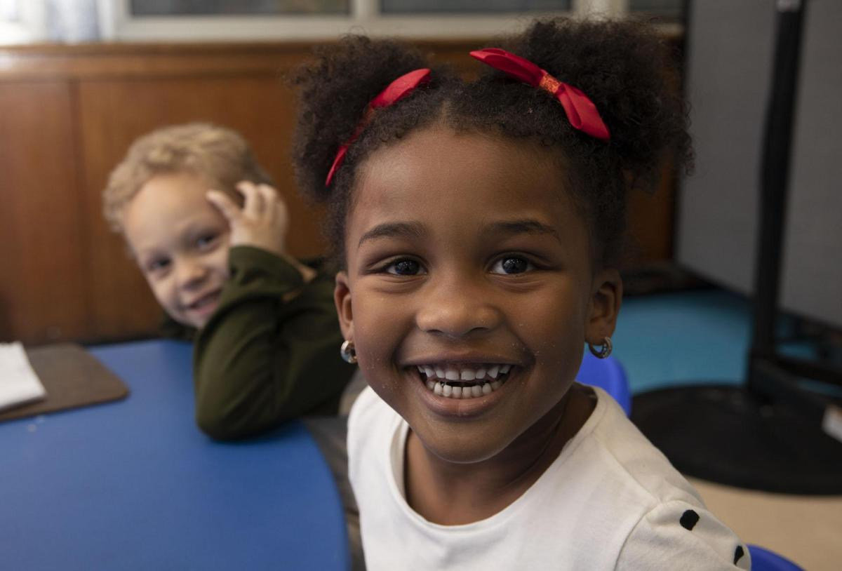 Girl and boy sitting in class with big smiles