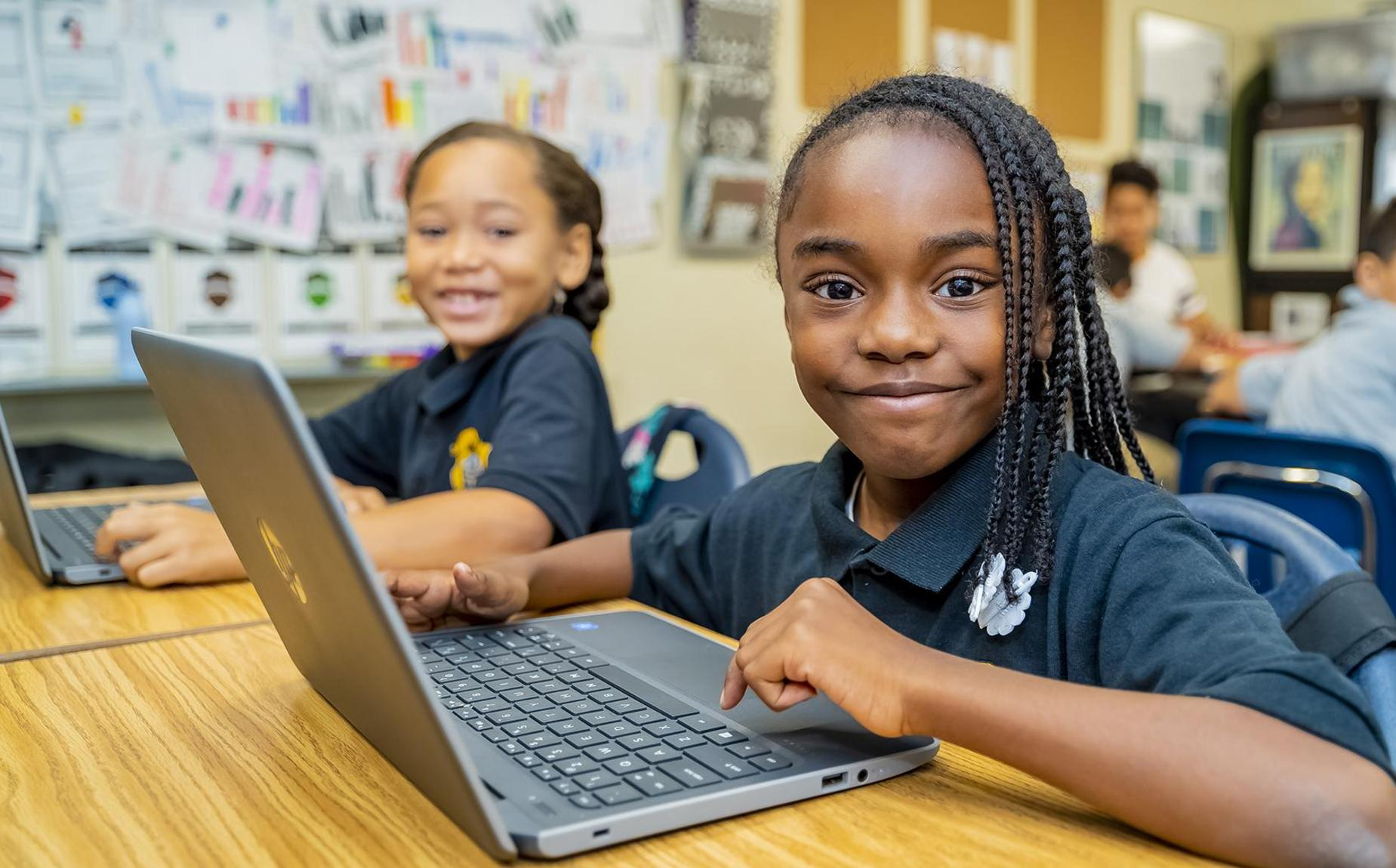 2 Students with Computers at their desks in classroom and smiling at the camera.