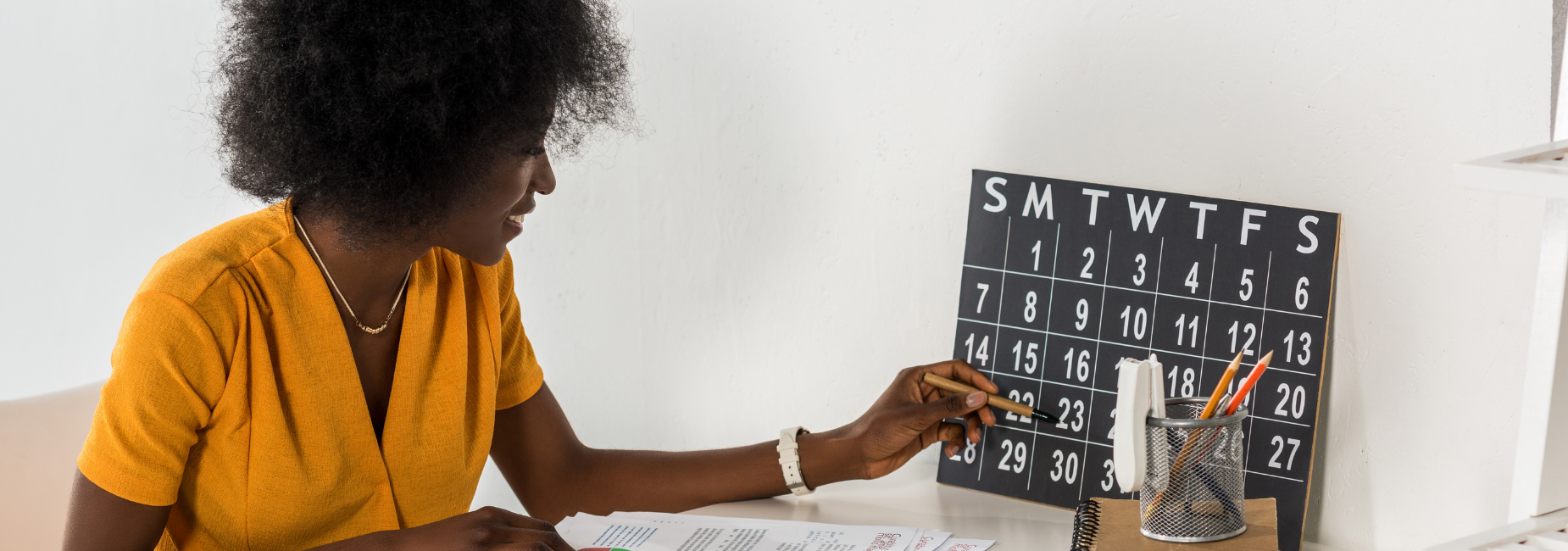 woman at a desk pointing to a date on the calendar