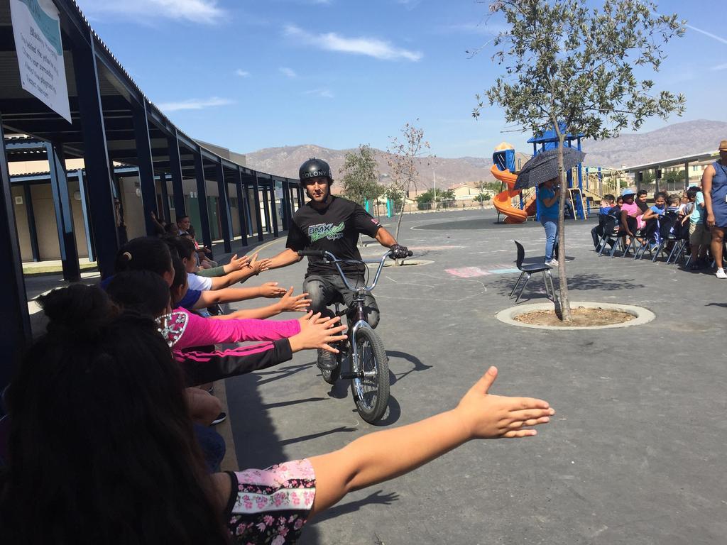 BMX rider high fiveing students