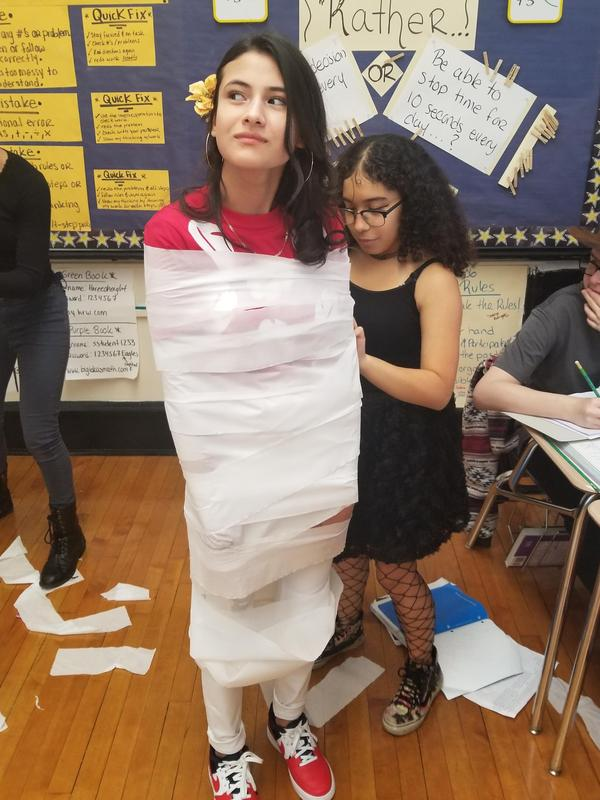 Girl being wrapped in toilet paper as a mummy by another girl