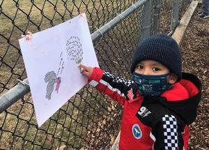 Photo of kindergartner reading one page of the playground Storywalk.