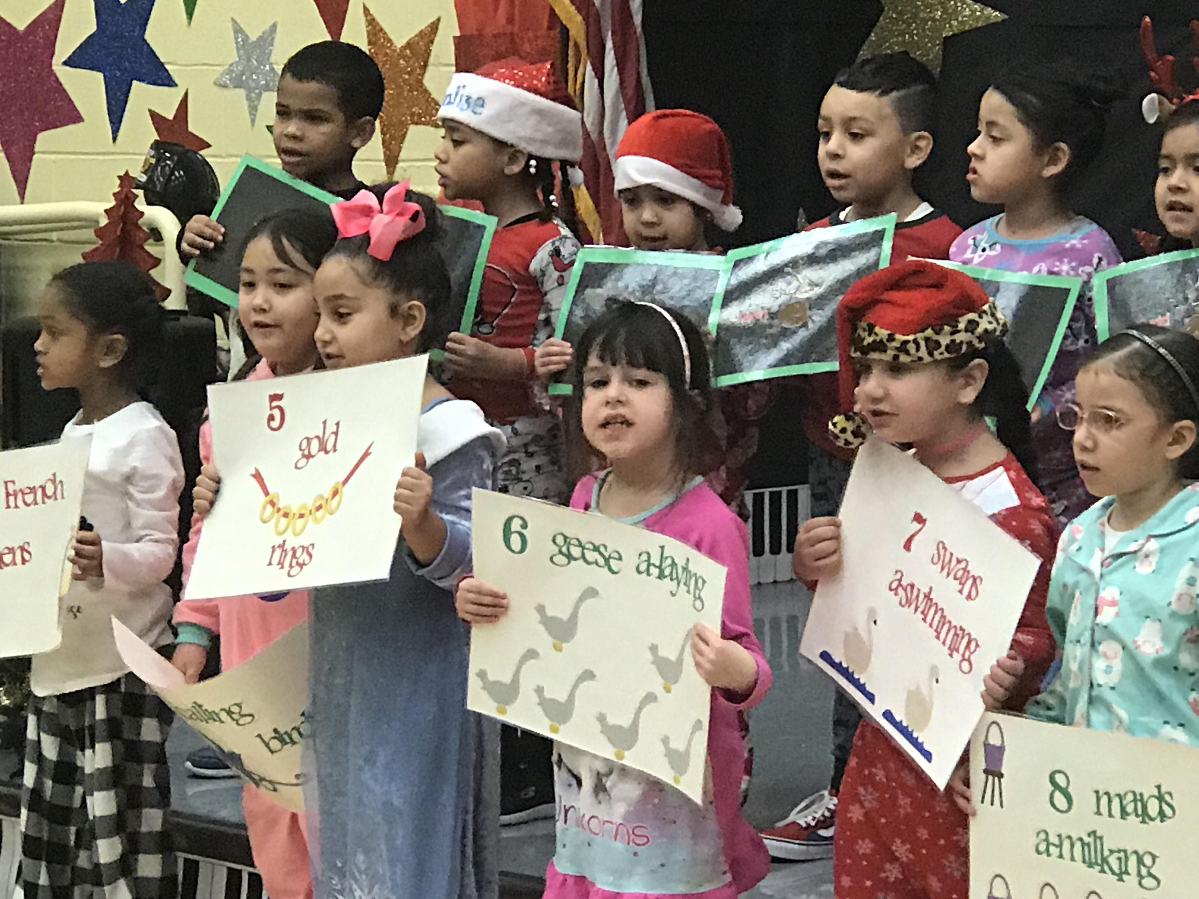 children holding up signs of the famous Christmas song