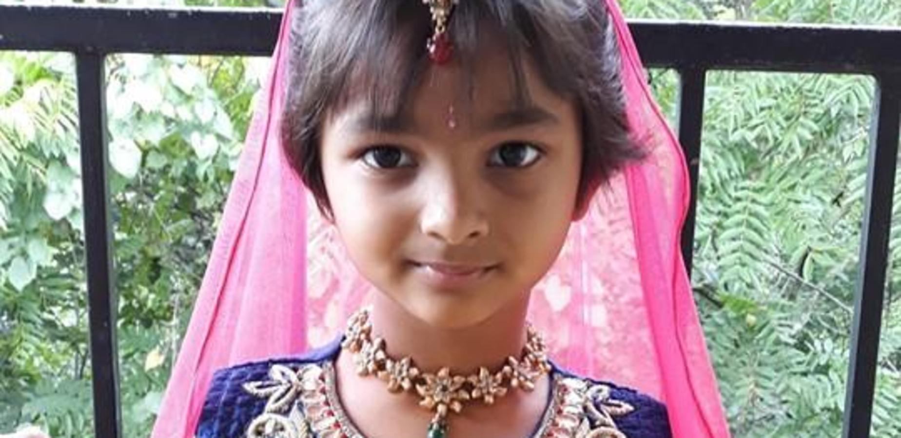 This is a photo of a student of Indian descent wearing the traditional dress of her family's country. She is wearing a pink head scarf with a jewel in the front, as well as a necklace and purple garment.