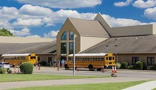 Picture of school building with a school bus out front.