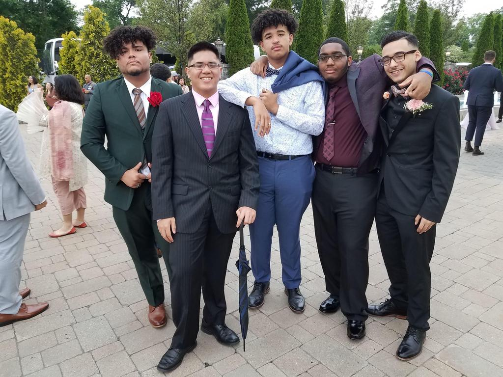 five students wearing suits smiling