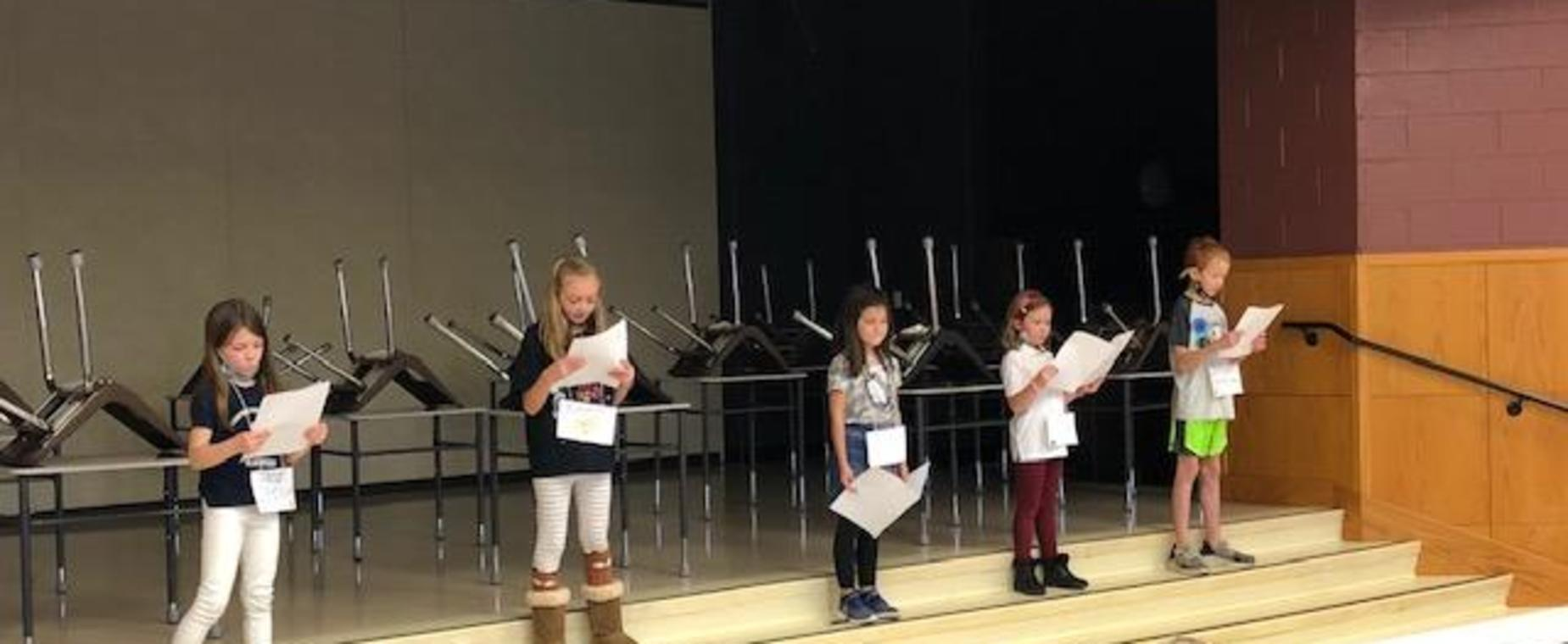 Second grade presents their stories to an audience of kindergarteners.
