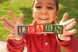Boy holding blocks that spell 'LEARN'