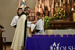 photo of Fr. Bill Dorner blessing the rings of the OLSH Class of 2021