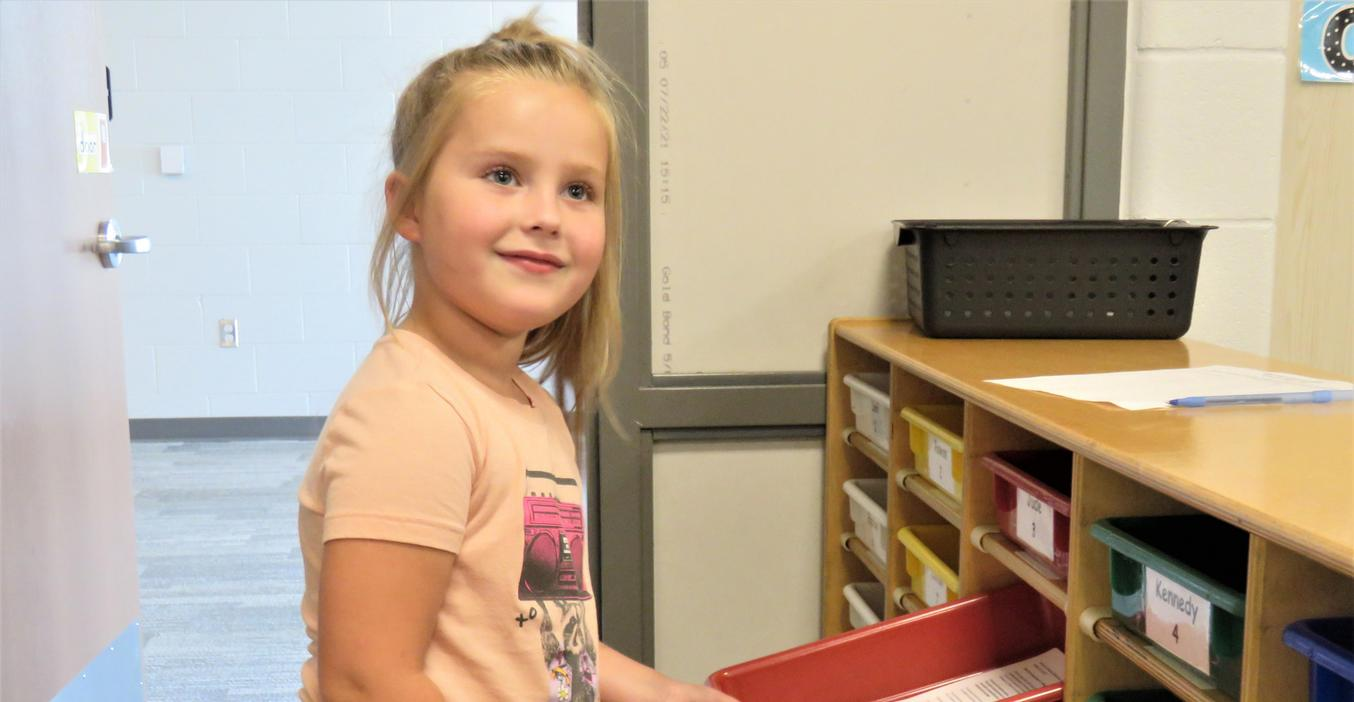A student finds her cubby during open house.