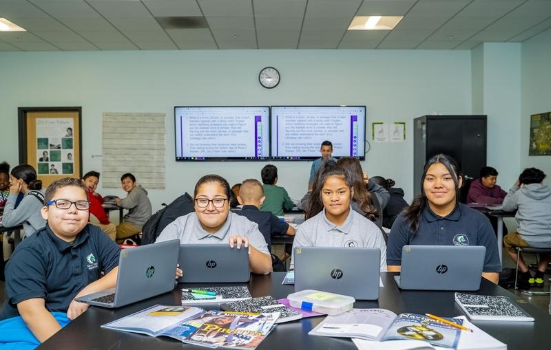 4 NVMS students smiling at the camera while sitting at their desks with laptops open in front of them in a New Vision classroom.