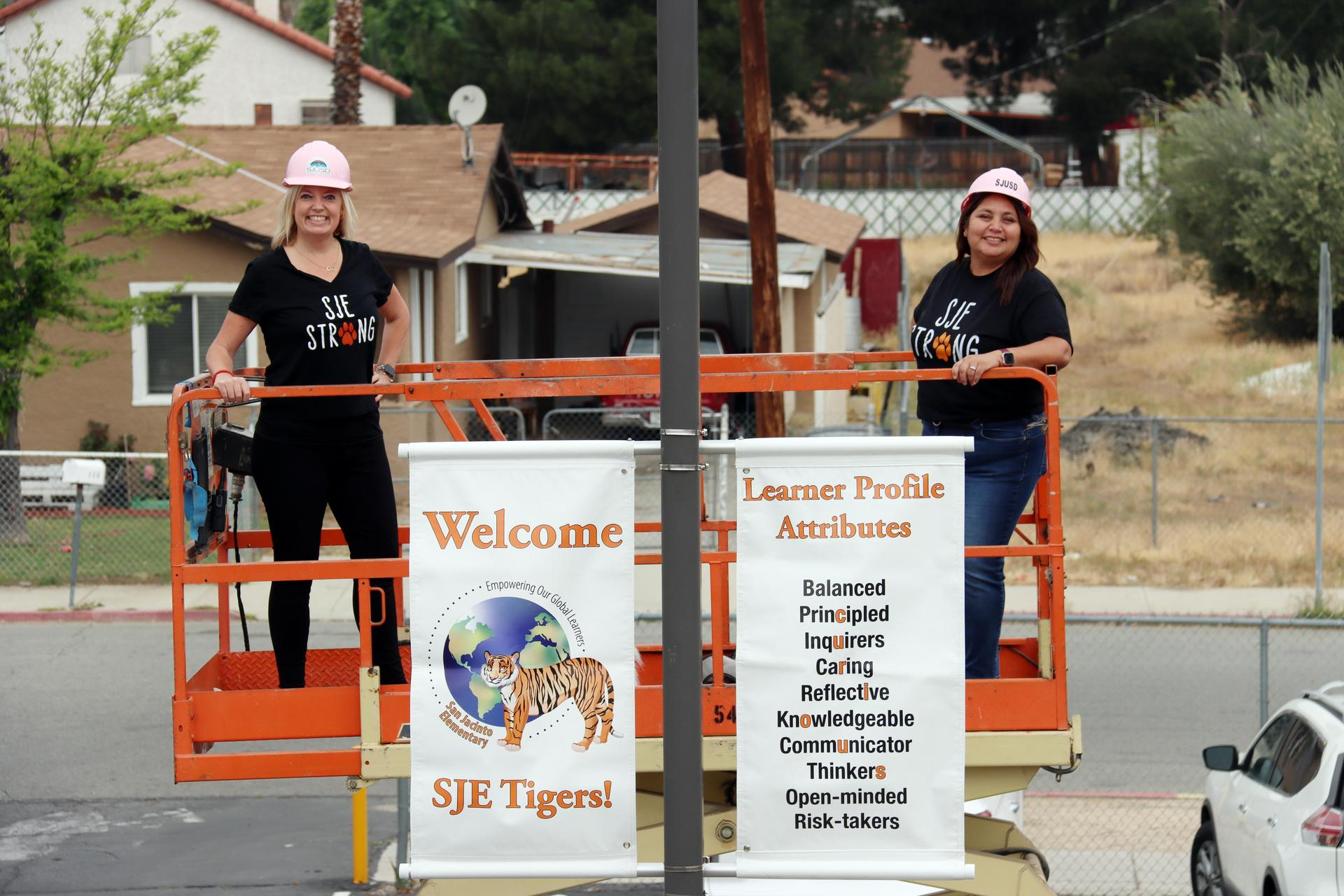Ms. Clines and Mrs. Portugal on a scissor lift hanging our new IB banners