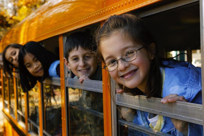 photo of bus with kids looking out window