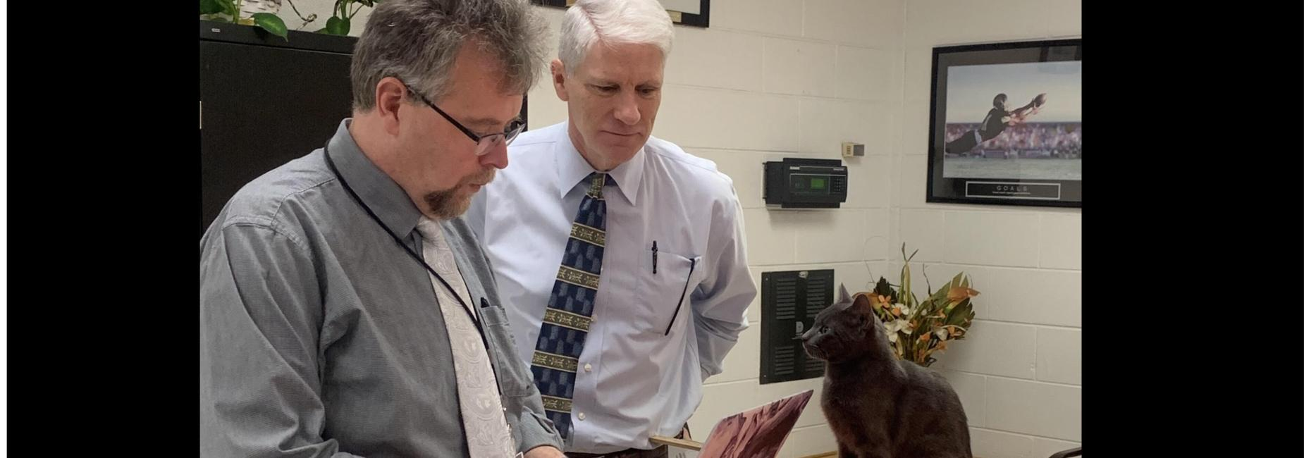 Thomas the office cat helping Mr. Berry and Mr. Blevins