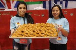 Two Middle School students holding large tray of pretzels at Cultural Unity Fair