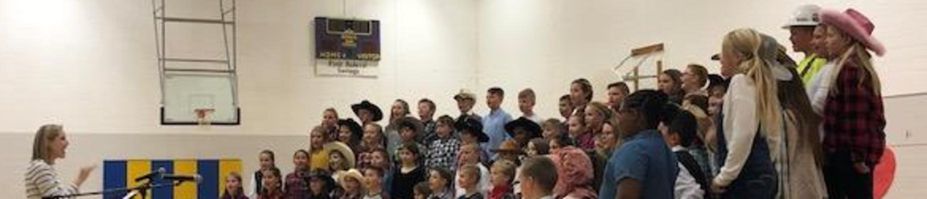 All 4th grade students standing on risers looking at music teacher, singing