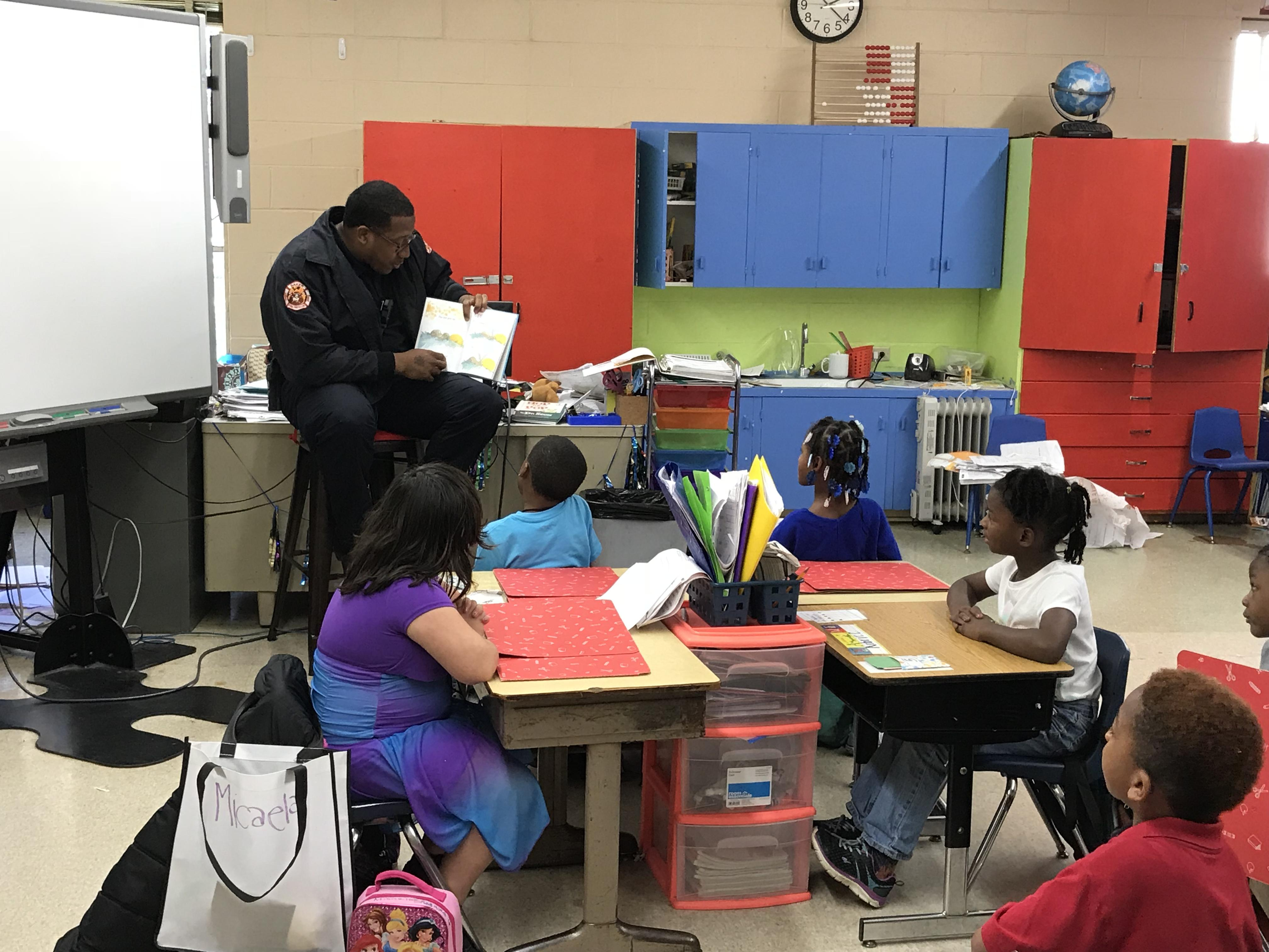a photo of another member of the Baker Fire Department reading to a classroom of students at Park Ridge Academic Magnet School