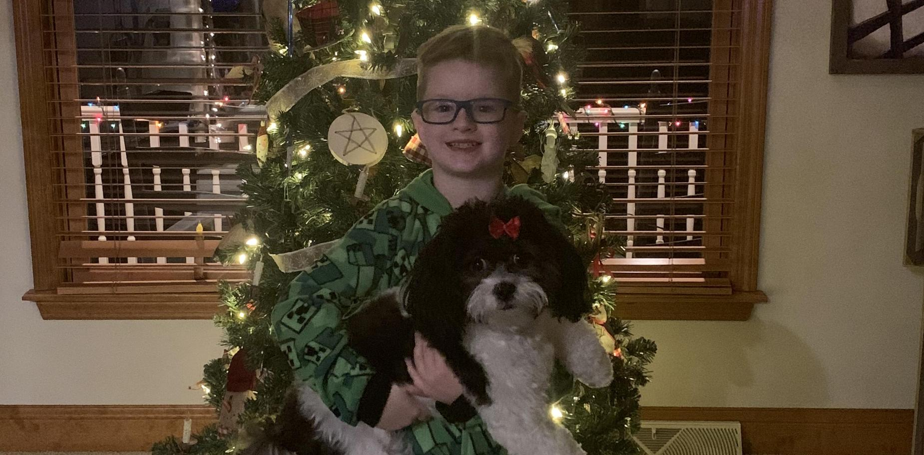 Child dressed in holiday attire holding a dog