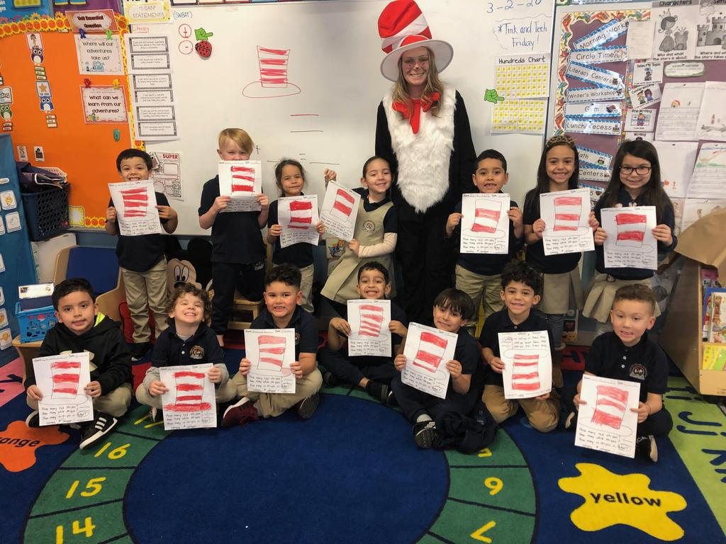 kindergarten teacher dressed as the Cat in the hat with her students holding up their cat in the hat poems