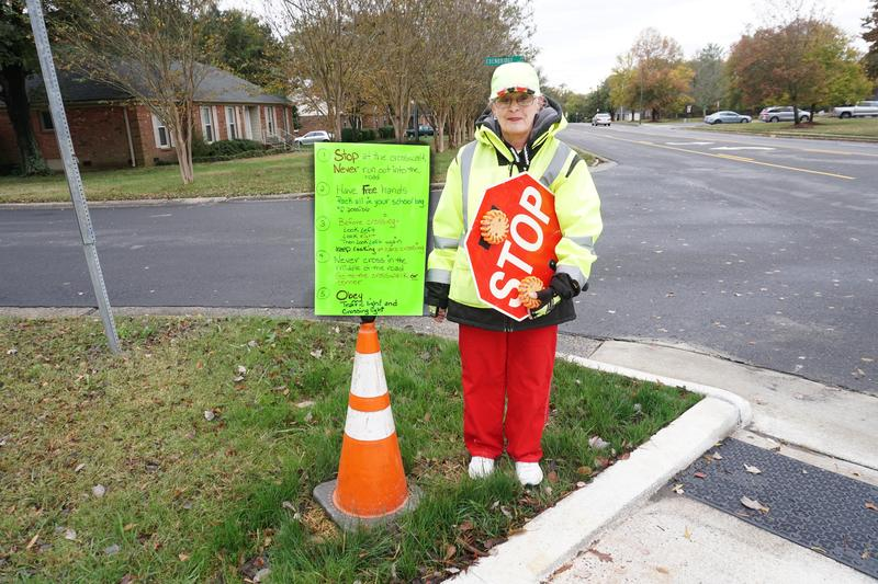 CMS crossing guard Sue Killar-Jordan in front of safety rule sign