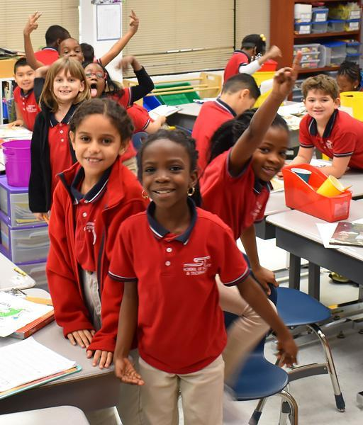Children in red polo shirts posing excitedly for the camera.