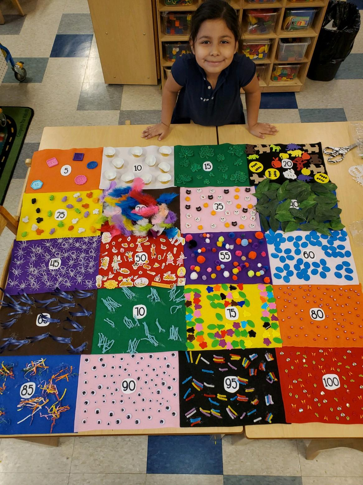 Girl in front of 100 Day quilt