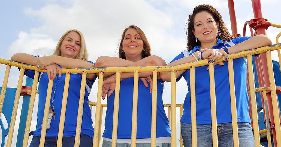 Three women standing on playground equipment smiling