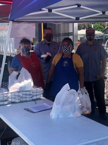 Members of the Nutrition Services staff wear 3-D printed face shields as they prepare meals for 5,100 community children. The shields were a gift from the Center for Innovation in STEM Education at Cal State Dominguez Hills.
