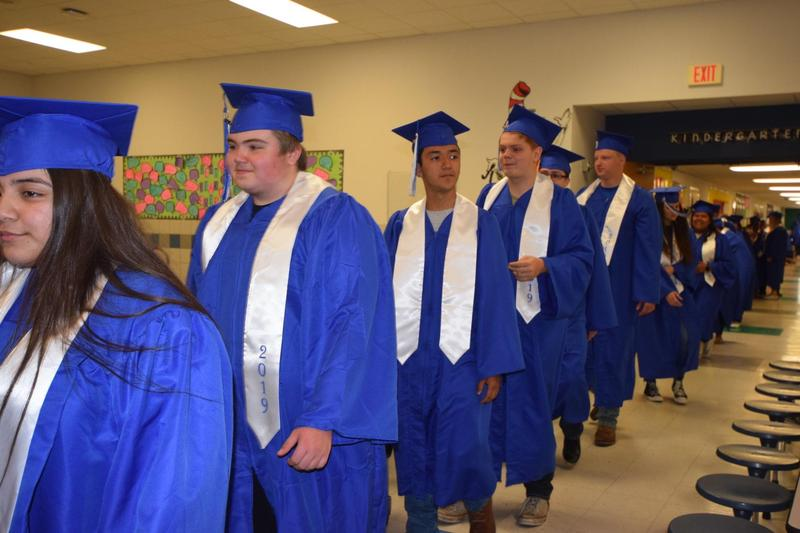 Graduates walking with DC Cannon students