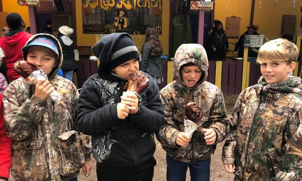 students eating a giant turkey leg