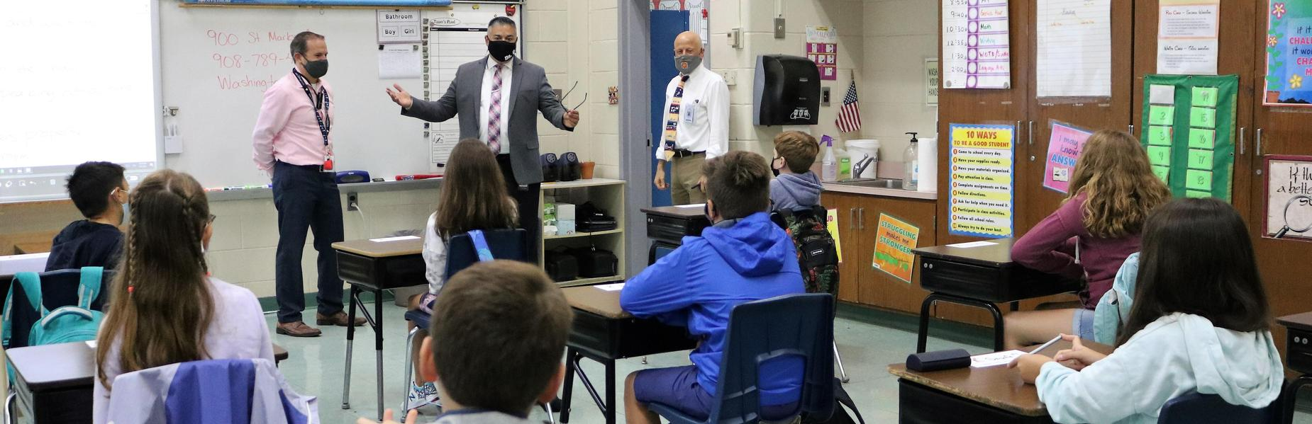 Photo of superintendent, principal, and teacher talking to 5th grade class.
