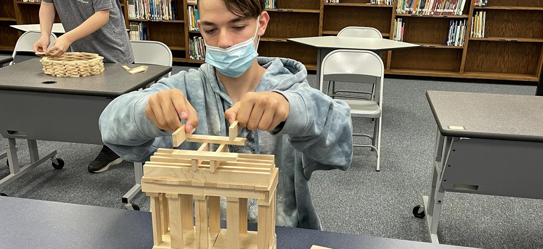 A student works with blocks in a library.